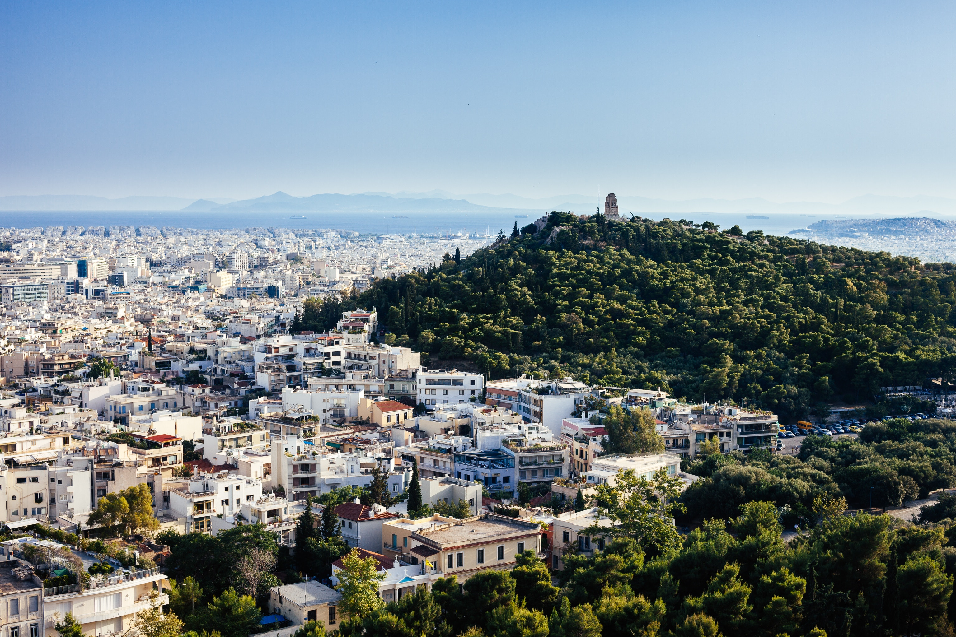 View of Athens from Lycabettus Hill in the City Center. Clear sky shows view of sea in South Athens and islands in Saronic Gulf.