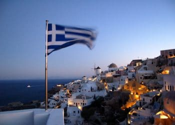 Santorini at night, with a Greek flag in the foreground