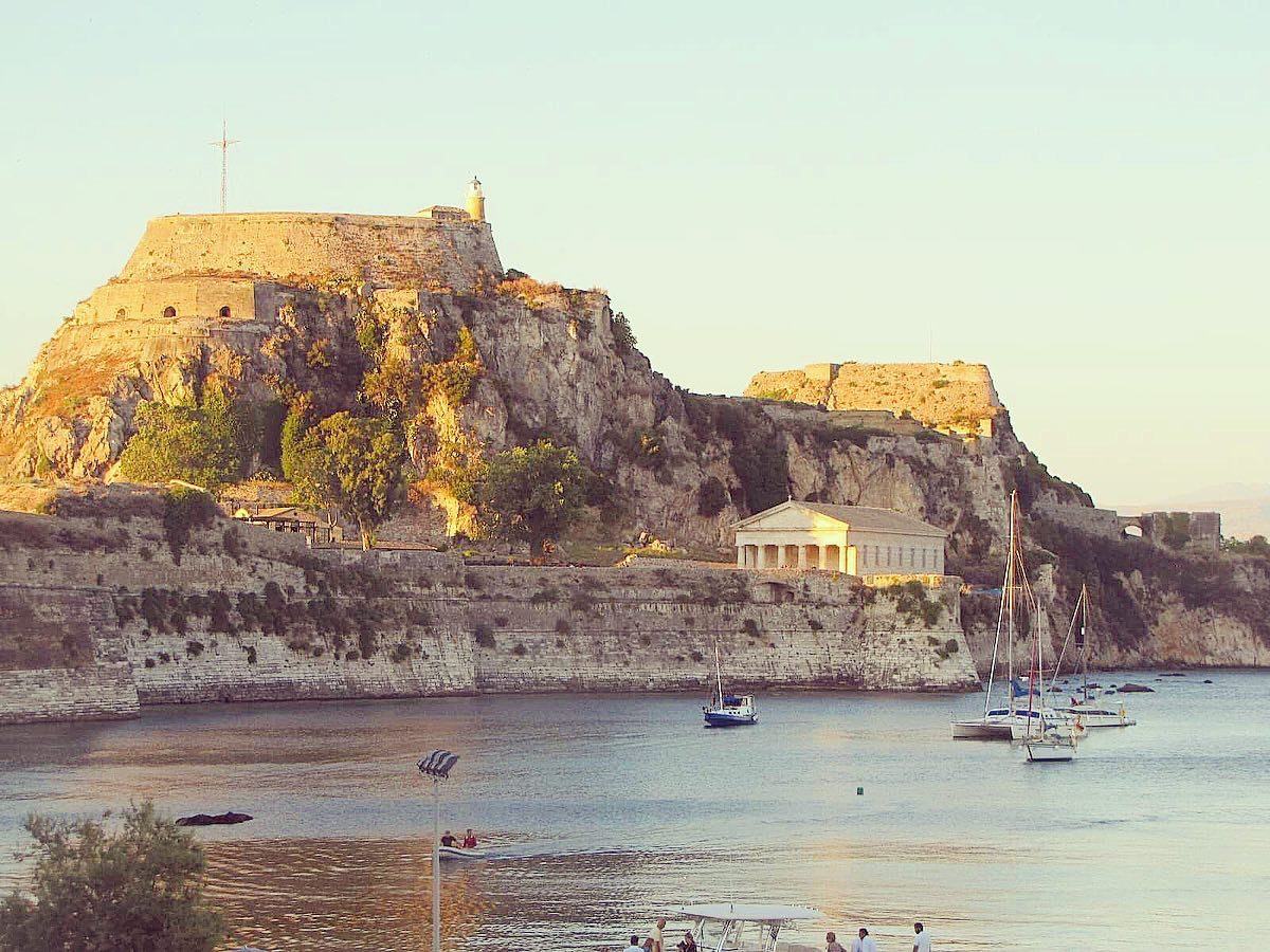 Corfu, Kerkira in the Ionian islands in Greece. View from a quiet beach, overlooked by a castle, the Old Fortress, and a temple.