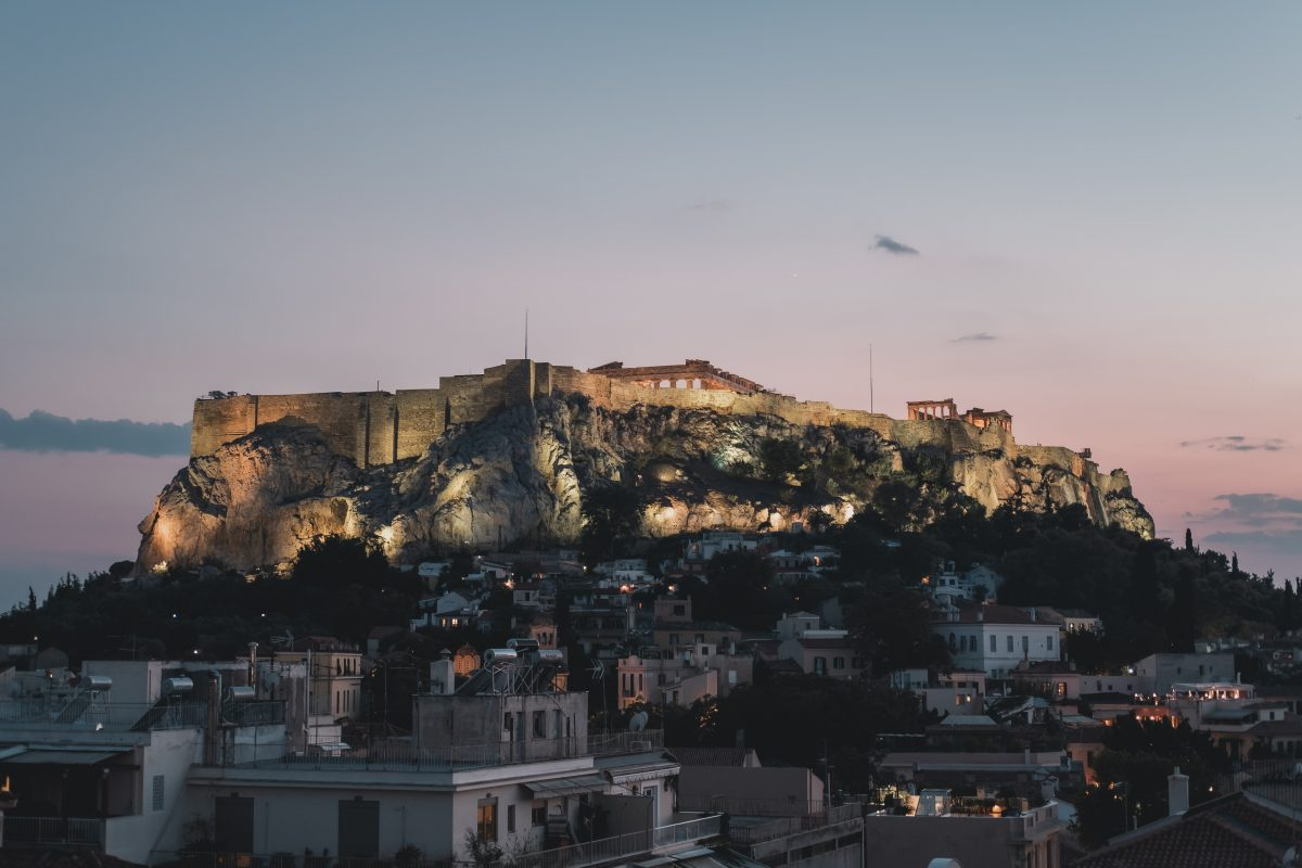 Night view of the Acropolis rock in Athens during sunset. The lights on the rock are illuminating the Parthenon temple.