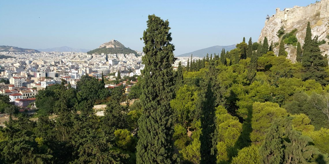 View of Athens on a sunny day with a clear sky showing Lycabettus Hill, the Acropolis rock and the dense greenery of Filopappou hill in the foreground
